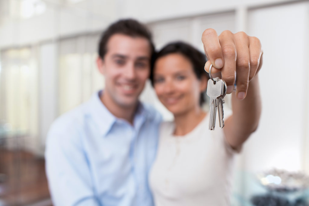 Happy,Smiling,Young,Couple,Showing,A,Keys,Of,Their,New