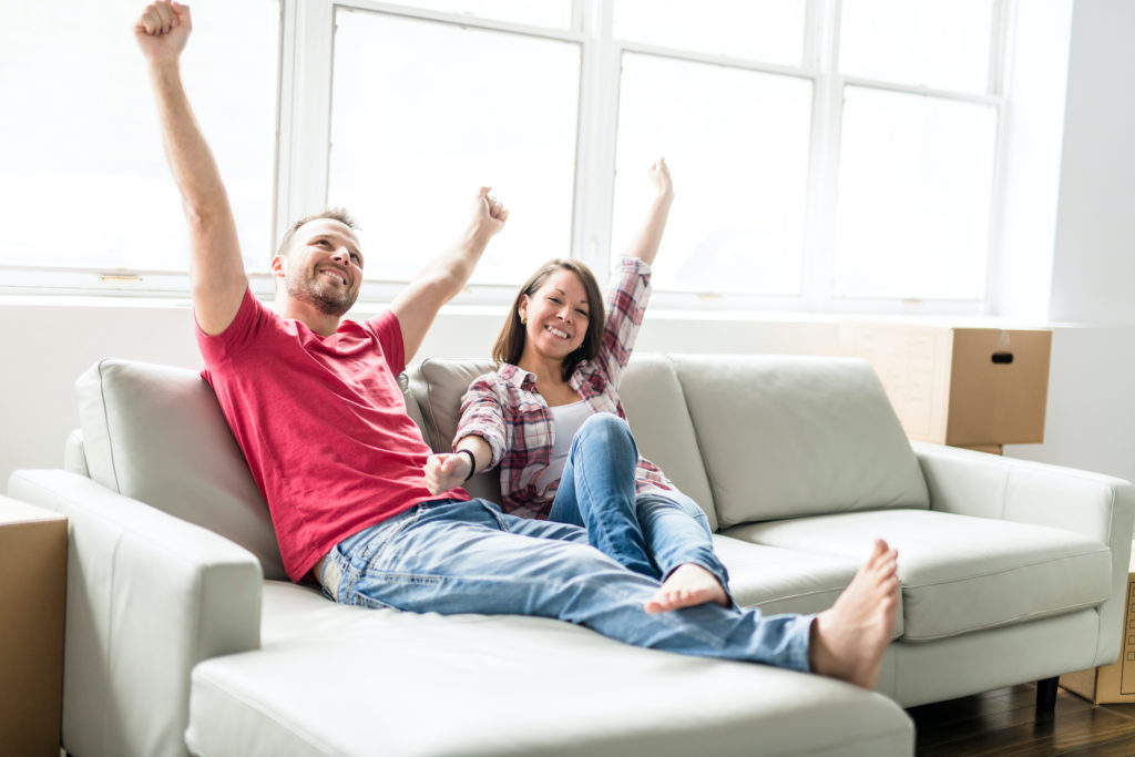 Couple,Sitting,Together,On,Sofa,At,Home,Happy,To,Move